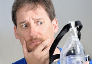 Man unsure of wearing CPAP device.