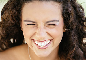 girl with eyes closed, laughing