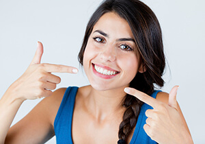 woman pointing to her straight teeth